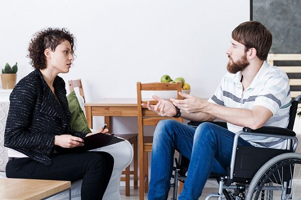 Young bearded man in wheelchair talking receiving treatment from a psychotherapist, treating attachment disturbances in adults episode with David Elliott